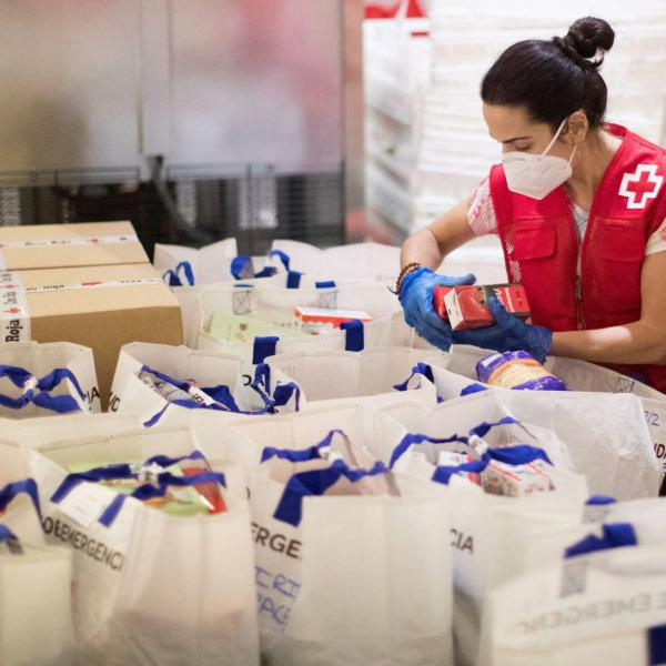 Una voluntaria prepara paquetes de alimentación básica en el almacén de la Cruz Roja en Barcelona. MARTA PÉREZ EFE